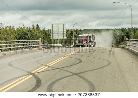Giant red dump truck makes it way down to the trans canada on road with tire markings