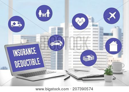 Modern workplace with laptop in office. Text INSURANCE DEDUCTIBLE on screen