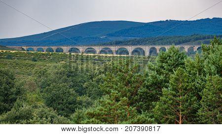 Long shot of long stone bridge in the wilderness