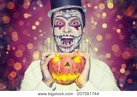 Halloween party theme. Portrait of man in mask for Halloween in black hat and angry pumpkin in hand. He is ready for Halloween party. Night halloween party concept. man dressed in Halloween costume.