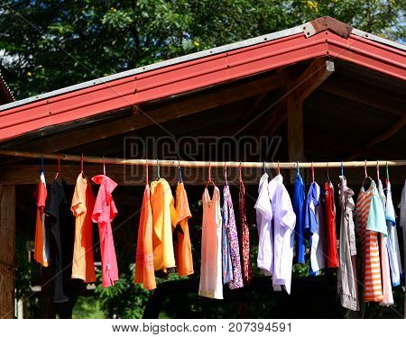 Many Clothes Hang On Bamboo Bar  To  Drying With Sunlight