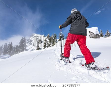 Man trekking in fresh deep powder snow to successfully summit mountain summit