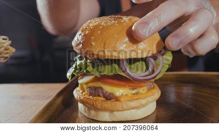 Chef making burger. Close-up shot of chef's hands preparing a delicious hamburger with beef rissole and cheese. Cooker putting bun on burger