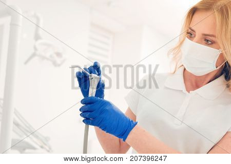 Attentive examination. Close up of female stomatologist standing at a clinic and focusing on a dental tool while checking it before starting her working day and treating the patients.