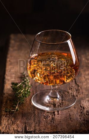 Glass of brandy or cognac with ice on old oak wooden table. Dark photo.