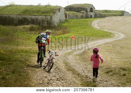 Girl running for catch her father who left behind she alone. Family cyclo holidays around town of Palmanova and its defense walls and trenches, Friuli Venezia Giulia region of Italy. poster