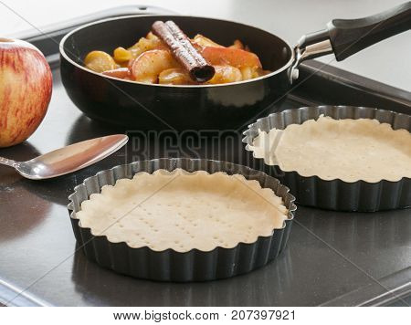 Work with the dough. Form for baking and ingredients for apple pie. The process of preparation of apple tart. View from above. Flat lay.