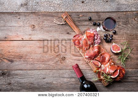 Sliced jamon on cutting board with fig , grapes and red wine. Parma ham hamon on wooden background with copy space, top view. Jamon Serrano Iberico. Traditional Spanish ham