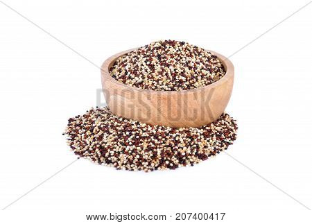 dry tricolor quinoa in wooden bowl and on white background