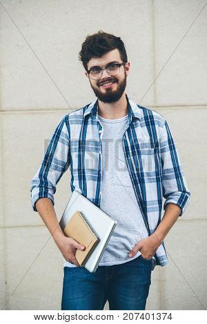 Portrait of smiling handsome university student with laptop and textbook