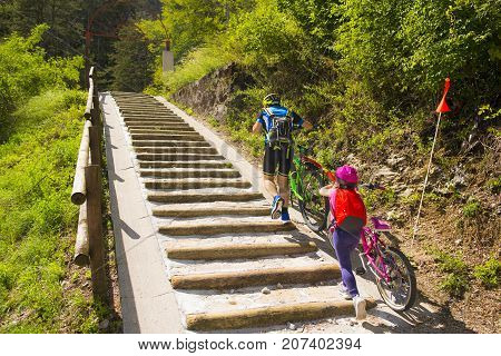 Father and daughter climb the steps with bicycle. Tandem, family cycling in Alpe Adria itinerary - Friuli-Venezia Giulia, Italy