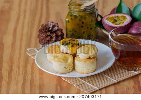 Homemade plain scones serve with homemade passion fruit jam. Scones is English pastry for afternoon tea. Delicious scones in Devon shire or Cornish cream style for tea time. Scones and jam with tea ready to served on table with copy space.