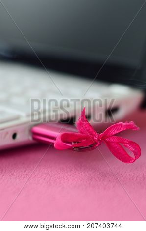 A Brilliant Pink Usb Flash Drive With A Pink Bow Is Connected To A White Laptop, Which Lies On A Bla