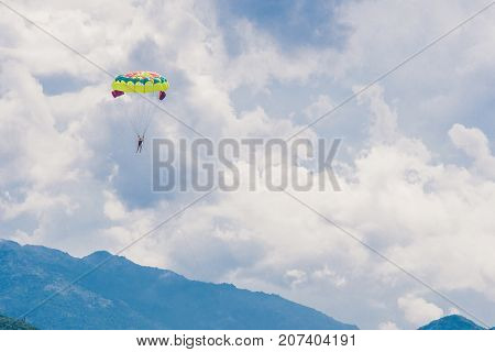 Young Woman Flies On A Parachute Among The Clouds