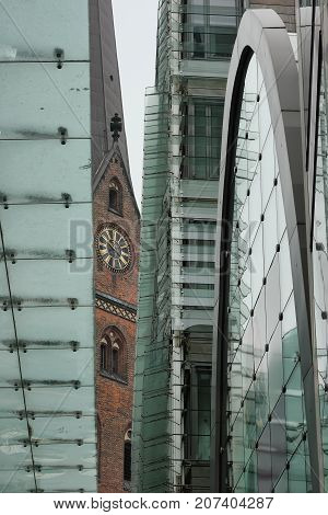Unusual cityscape of Hamburg. View of the St. Peters church through the elements of a modern building.
