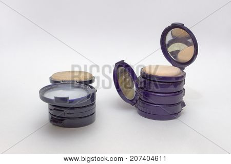 Compact Powder Boxes In Vertical Stacks, Opened Cases Contains Mirror And Powder Puff