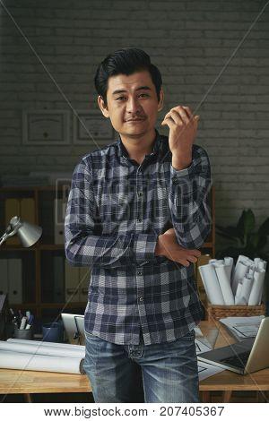 Portrait of confident Vietnamese engineer standing in architecture bureau