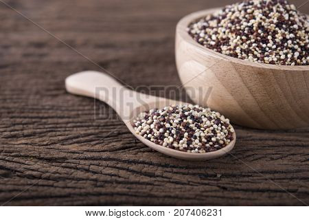 dry tricolor quinoa in wooden spoon and bowl on wooden background