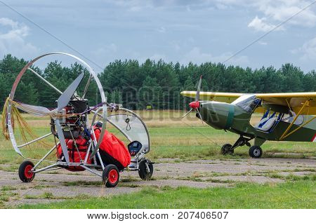 TOURIST PLANES AND ULTRALIGHT TRIKE -  Machines flying on a grassy airport