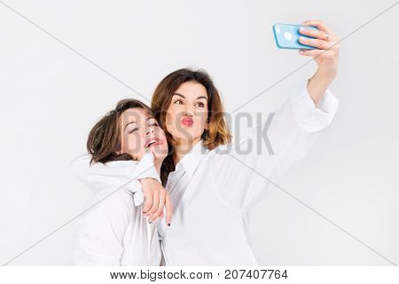 Two women posing taking selfie in light studio. Girls best friends making funny grimaces on camera, showing tongue and laughing together
