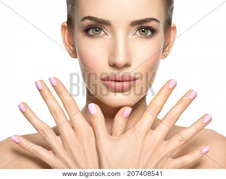 Beauty face of the young beautiful woman - isolated on white. Female with nice fingernail. Pretty young girl shows hands before face with a pink nails