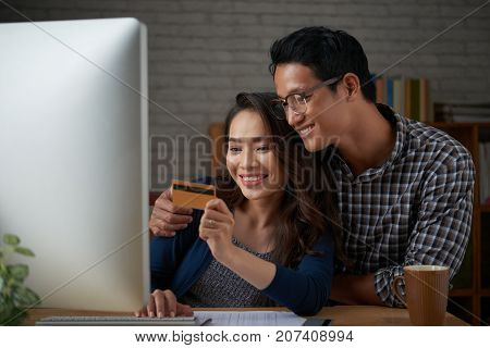 Beautiful couple entering information from credit card to pay for online purchase
