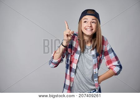 Emotional happy teen girl shrugging shoulders and pointing to the side up at empty copy space, over grey background.