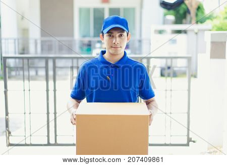 Delivery concept - Portrait delivery person in blue uniform holding cardboard box standing in front the home customers.