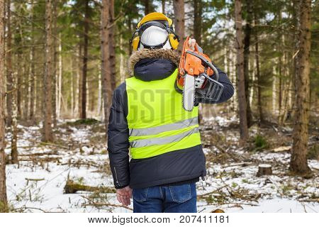 Lumberjack with chainsaw on shoulder in forest