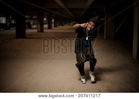 Emotional full length portrait of the gesticulating afro american man with dreadlocks and dressed in black clothes