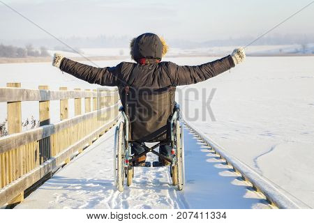 Happy disabled man on wheelchair in winter day