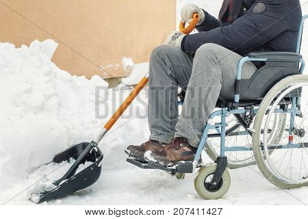 Disabled man on wheelchair with snow showel in the yard