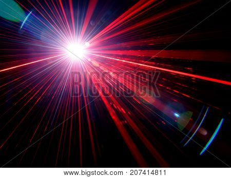 Red stage light effect with lens flare on black background, photo.