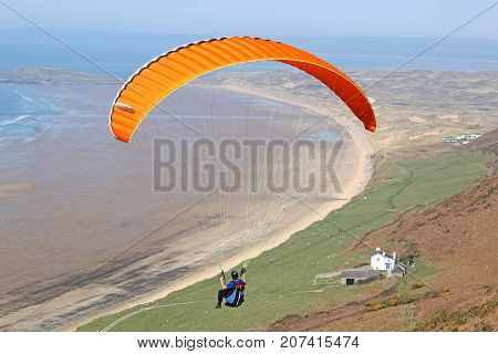 Paraglider flying above Rhossili beach in Wales