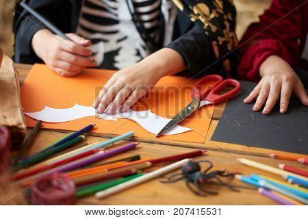 Hands of child outlining bat stencil on orange paper