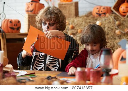 Boy in Halloween costume cutting out of orange paper with enthusiasm