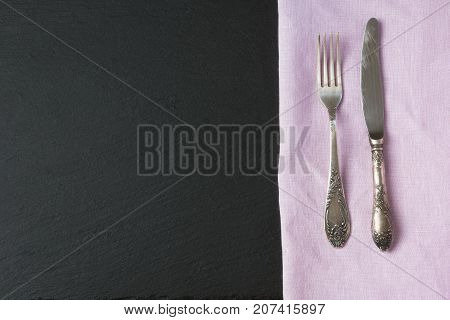 Silverware On Linen Napkin And Black Slate Dish With Copy Space For Your Menu Or Recipe. Top View.