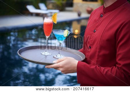 Cropped image of waiter bringing tray with colorful cocktails
