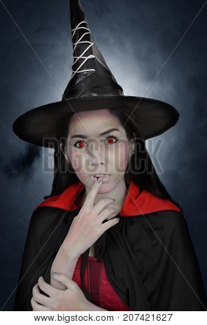 Vampire in witch suit with red blood on her lips in front of dark clouds and moonlight.