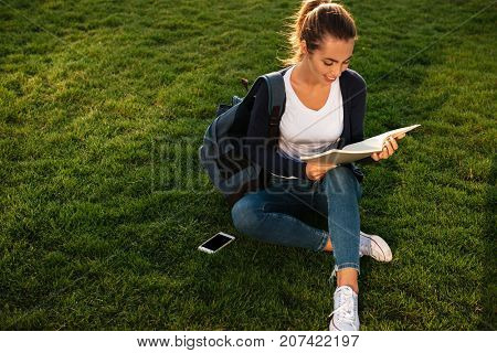 Portrait of a casual young student girl with backpack reading textbook while sitting on the grass at park