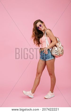 Full length portrait of cheerful readhead woman in summer wear with backpack posing with hands in her pockets, over pink background