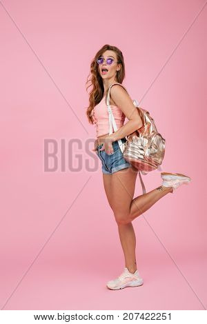 Full length portrait of amazed readhead woman in summer wear with backpack, standing on one leg with hands in her pockets, over pink background