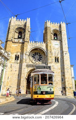 Lisbon, Portugal - August 25, 2017: tourists on historic Tram 28, most famous tram line, in front of Lisbon Cathedral in Alfama district. Lisbon street with typical yellow tram and Se de Lisboa.