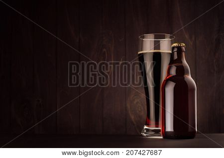 Brown beer bottle belgian steinie and glass weizen with porter on dark wood board copy space mock up. Template for advertising design branding identity.