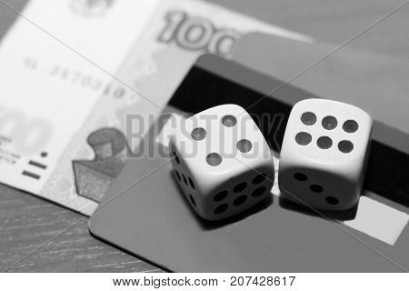 Two Dice Laying Over A Pile Of Money