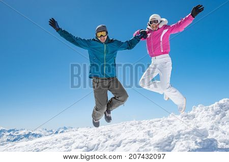 Young couple playing with snow outdoor in a winter day. Happy woman and man in ski suit jump on snowy mountain. Happy young couple in love jumping and having fun in winter holiday.
