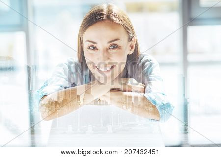 Looking great. Close up of marvelous optimistic business woman smiling while keeping head on crossed arms