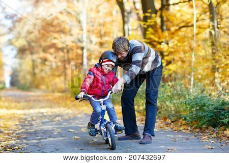 Little kid boy and his father in autumn park with a bicycle. Dad teaching his son biking. Active family leisure. Child with helmet on bike. Safety, sports, leisure with kids concept.