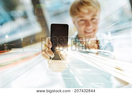 Best choice. Pleasant man holding fashionable expensive mobile phone and showing this magnificent device to you