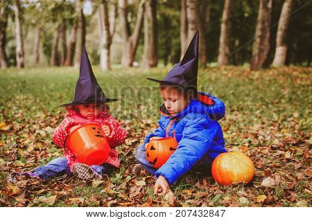 kids in halloween costume play at autumn, trick or treating